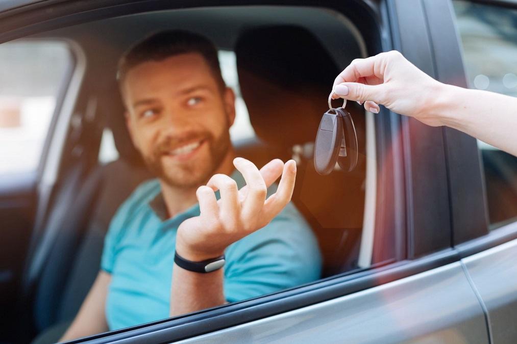 Beautiful bearded man receiving car keys